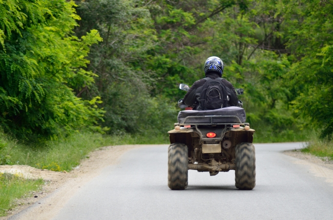 A Young Man Driving an ATV on a Road
