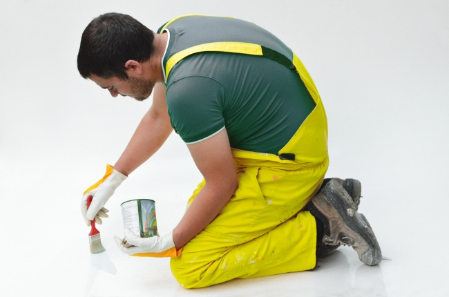 Blue-Collar Worker Painting a Floor