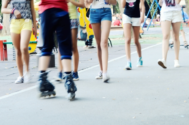 Group of Teenagers Passing By the Playground on a Summer Day
