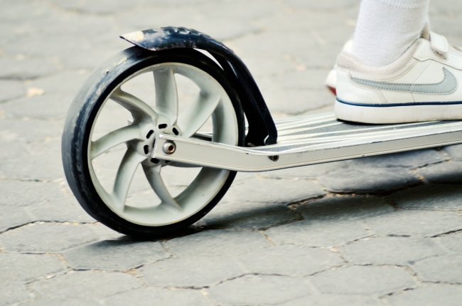 Child Stepping on Kids' Scooter on Pavement