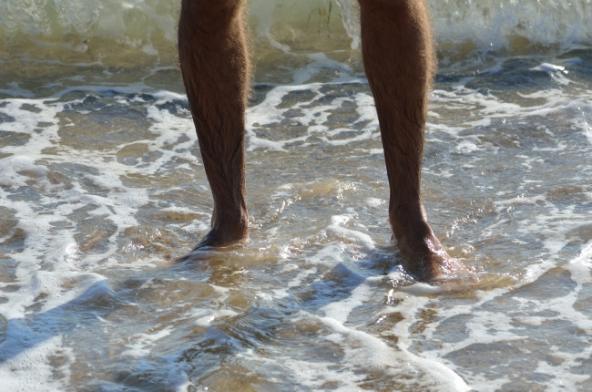 Sea Wave Hitting the Legs of a Man