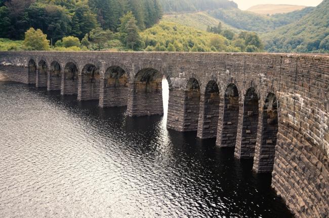 Pre-Industrial Rock Bridge over a Calm Water