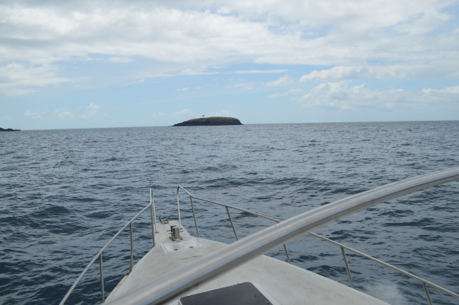 A Small Isolated Island on the Sea Seen From a Boat