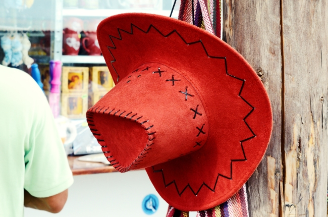Suede Red Hat and Colorful Fabric Hanging in front of Gift Shop