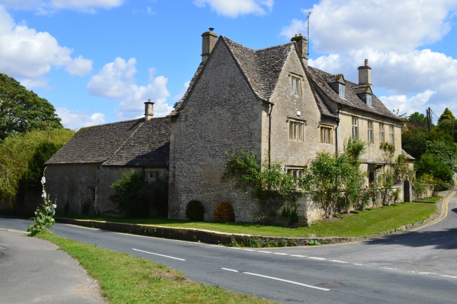 House with Roses and Other Vegetation in Bibury, UK
