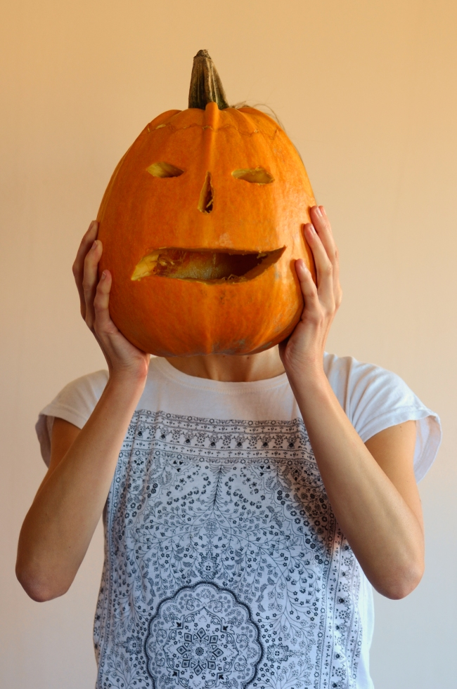 Woman Holding Jack-O'-Lantern Head in front of Her