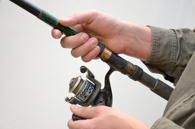 Checking the Fishing Reel of a Green Rod