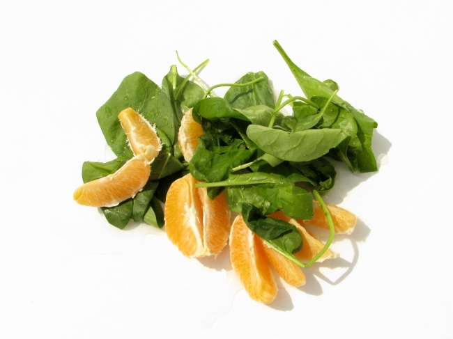 Tangerine and Spinach Leaves on White Background