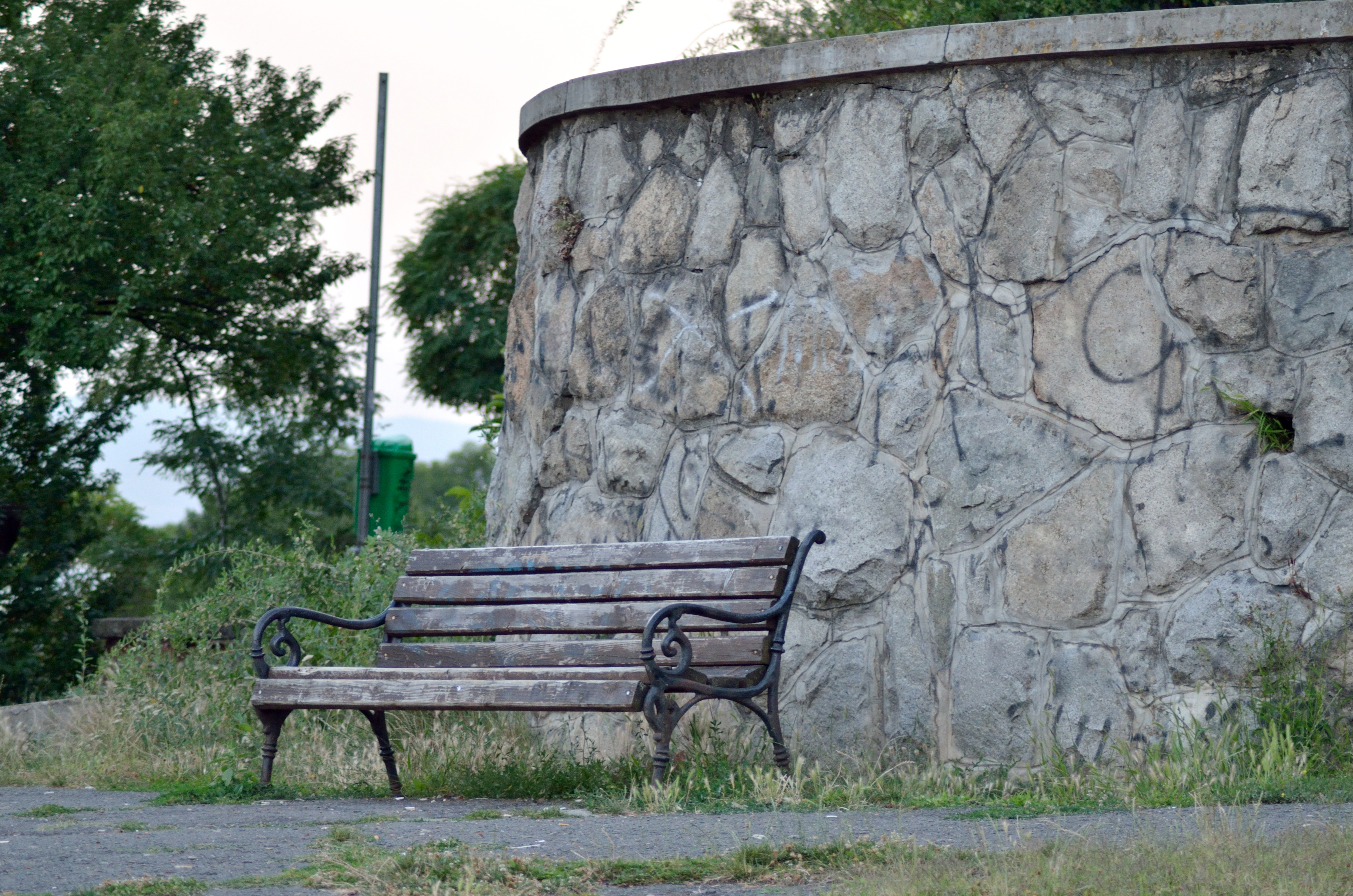 Wooden Bench In Front Of An Old Wall In A Park Gimmeges