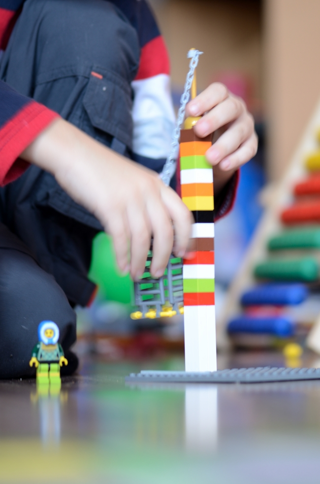 Kid's Hands Building LEGO Tower