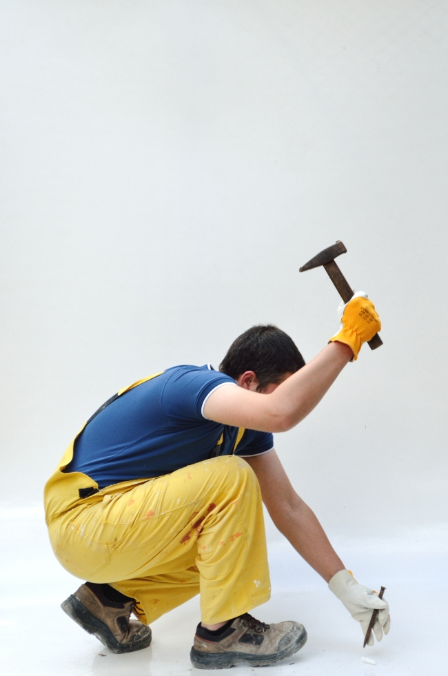 Man in Yellow Overall with Hammer and Nail