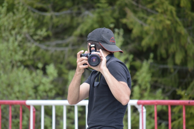 Young Man with Hat Taking Pictures