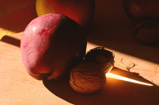Walnuts and Red Apple in Afternoon Light