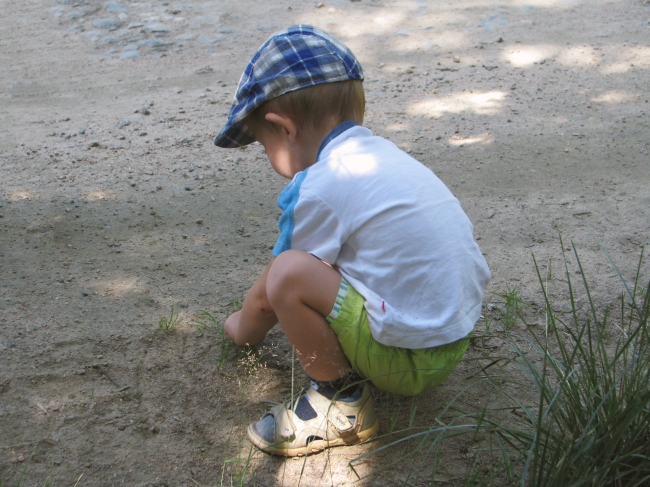 Young Boy with Checkered Hat Playing on Sand